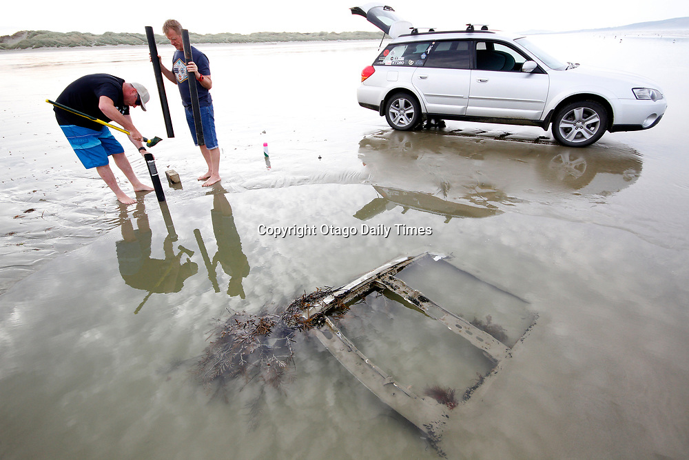 A super moon that resulted in a very low tide revealed a  a buried car at Invercargill's Oreti Beach. Concerned that surfers or swimmers might be injured by the car wreck, one local surfer (who declined to be named) and fellow surfer Dr Mark Rudel (right) hammer a pole into the sand to warn other water users of the dangers that lurk there, until Invercargill City Council officials have had a chance to get a digger in remove the wreck. PHOTO: GIORDANO STOLLEY/ Otago Daily Times (Note: This image can only be purchased directly from the Otago Daily Times)