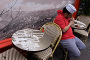 A chef lights a cigarette and relaxes at a table picturing the ancient ruins of Gerrha, in front of a panorama of the Bekaa Valley in Lebanon outside a Lebanese cafe in London's Soho. The panoramic landscape of this Lebanese landmark plus the juxtaposition of the ruins make an incongruous detail in this modern central London street known for its restaurants, cafes and media businesses.