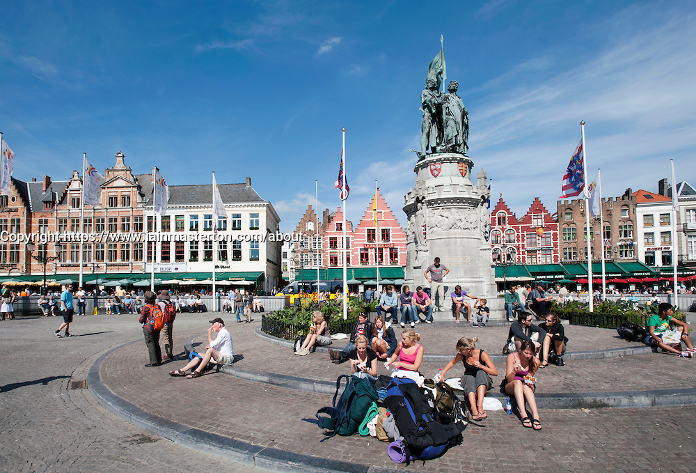 Tourists sitting in Market Square in Bruges in Belgium