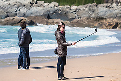 A woman takes a selfie on Fistral Beach in Newquay, Cornwall.