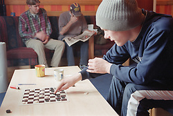 Residents playing draughts and reading newspaper in communal lounge of Young Persons' Resettlement hostel,