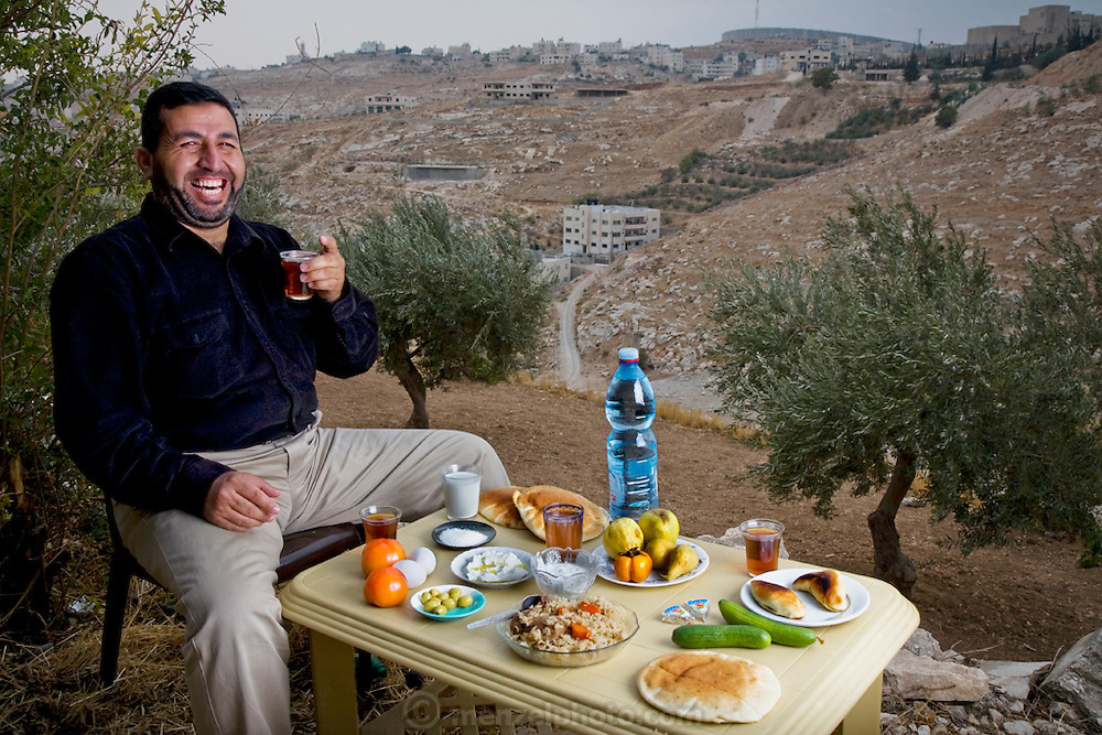 Abdul-Baset Razem, a Palestinian guide and driver in his extended family's backyard olive orchard with his day's worth of food in the Palestinian village of Abu Dis in East Jerusalem. (From the book What I Eat: Around the World in 80 Diets.) The caloric value of his typical day's worth of food on a day in the month of October was 3000 kcals. He is 40 years of age; 5 feet, 6 inches tall; and 204 pounds. On the hilltop in the distance, Israel's 25-foot-high concrete security barrier cuts off this Abu Dis neighborhood from Jerusalem, turning a short trip into the city into an extremely long and circuitous journey requiring passage through an Israeli checkpoint on the highway. Constructed by the Israeli government to cut down on attacks and suicide bombings, the highly controversial 436-mile-long barrier was 60 percent complete at the time of this photo. For the majority of Palestinians, travel to and from East Jerusalem now requires special permits from the Israeli government?often difficult or impossible to obtain. MODEL RELEASED.