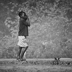 Um rapaz a apreciar o movimento de pessoas e bens na estrada que leva até as Quedas de Calandula. Província de Malange, Angola