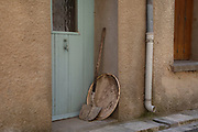 Garden shovel chair in a doorway in Termes, France. Termes is a commune in the Aude department in southern France.