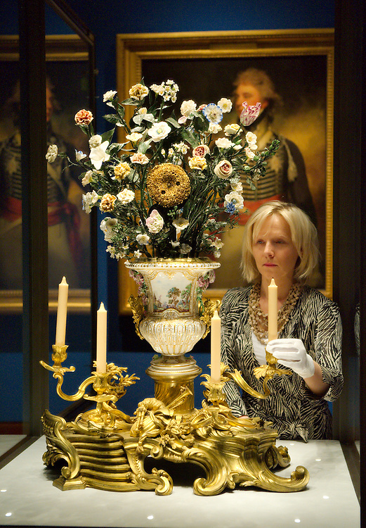 LONDON, ENGLAND - MAY 22:  A  member of staff from the Royal Collection put some final touches at a Vincennes Sunflower Clock (1752)  part of the Sevres  exhibition that will open May 23rd. On May 22, 2009 in London, England.  (Photo by Marco Secchi/Getty Images)