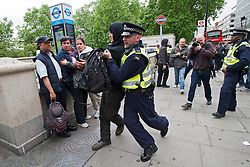 © London News Pictures. 11/06/2013. London, UK.  An Anti-G8 activist being detained  by police  ahead of an anti G8 demonstration in central London today (Tues). The G8 Summit is due to take place in Norther Ireland early next week.  Photo credit: Ben Cawthra/LNP