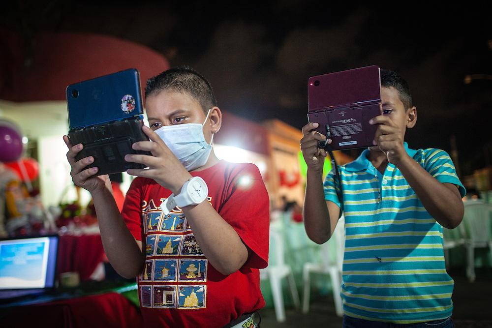 Manuel Alejandro Romero toma una foto con su Nintendo DS junto a su primo Jose Manuel (d) en el sector Lomas de Maracaibo. Gracias a FundaHigado, en junio de 2012, recibió un trasplante de higado que le permite disfrutar de la vida. Maracaibo, Venezuela 20 y 21 Oct. 2012. (Foto/ivan gonzalez)