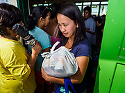 29 JANUARY 2018 - GUINOBATAN, ALBAY, PHILIPPINES: A woman who lives on Mayon volcano picks up a bag of donated rations at the shelter for evacuees from Mayon volcano in Mauraro National High School in Guinobatan. There are 1,773 people in the shelter. Mayon volcano's eruptions continued Monday. At last count, more 80,000 people have been evacuated from their homes of the slopes of the volcano and are crowded into shelters in communities outside of the danger zone.    PHOTO BY JACK KURTZ