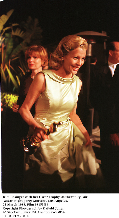 Kim Basinger with her Oscar Tony  at theVanity Fair Oscar  night party, Mortons, Los Angeles. 23 March 1988. Film 98155f36<br />Copyright Photograph by Dafydd Jones<br />66 Stockwell Park Rd. London SW9 0DA<br />Tel. 0171 733 0108
