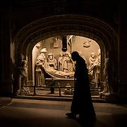 """A monk walks in front of the tomb of Our Lord located in the transept of the abbey church. This group of statues known as """"Saints de Solesmes"""" was completed in 1496 and depicts the passion and resurrection of Christ. 08-01-16<br /> Un moine marche devant le tombeau de Notre Seigneur situé dans le transept de l'église abbatiale de Solesmes.. Cet ensemble sculpté connu sous le nom de """"Saints de Solesmes""""a été achevé en 1496. Il est entièrement consacré à la passion et la résurrection du Christ. 08-01-16"""