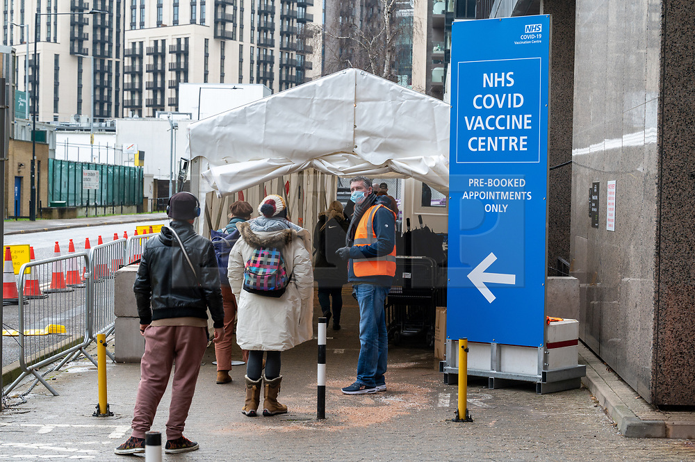 © Licensed to London News Pictures. 26/01/2021. London, UK. People walk into the  Olympic Office Centre, near Wembley Stadium to receive a Covid-19 vaccination jab. Today the Office for National Statistics (LNS) today revealed as of January 15 there had been 103,704 Covid deaths. Photo credit: Ray Tang/LNP