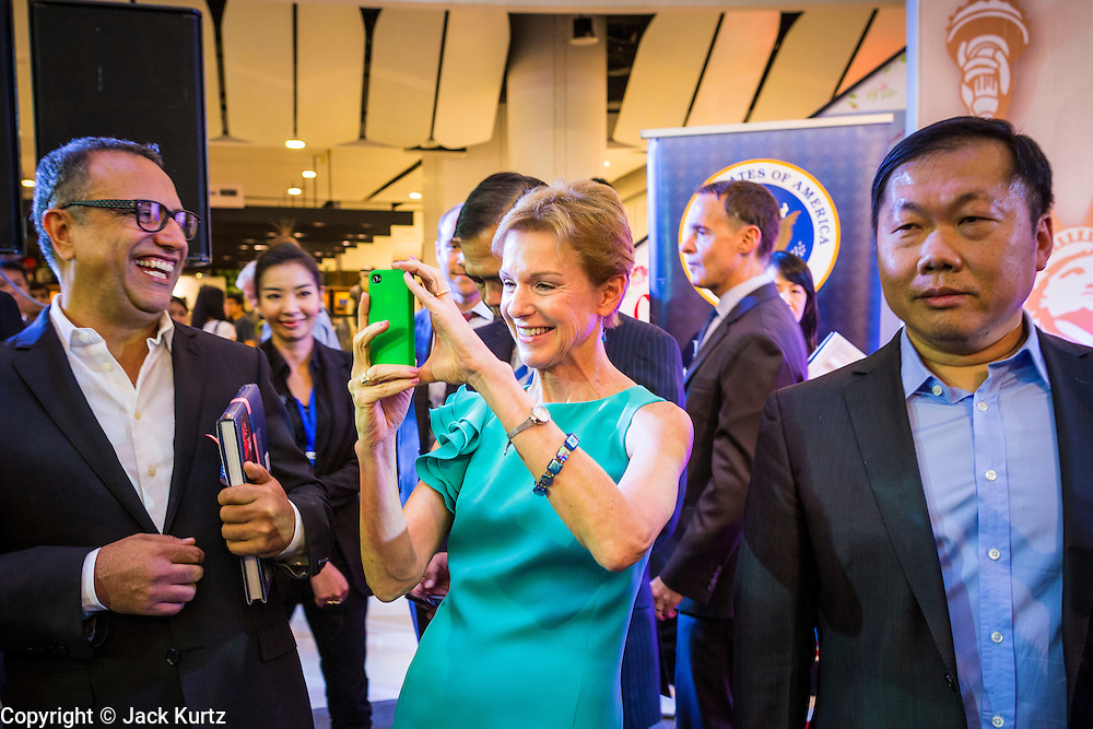 19 JULY 2013 - BANGKOK, THAILAND:  KRISTIE KENNEY, the US Ambassador to Thailand, uses her smart phone to take pictures at the opening of a photo exhibit sponsored by the US Embassy in Bangkok. The photo exhibit celebrates 180 years of US-Thai diplomatic relations. There are 180 photos hanging in the show, 90 by American photographers in Thailand and 90 by Thai photographers in the United States. The show, which opened July 19, is hanging in CentralWorld, a large mall in Bangkok, and is touring Thailand when it concludes its Bangkok run on July 21.    PHOTO BY JACK KURTZ