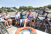 People sitting on River Deben foot passenger ferry boat at Bawdsey Quay, Suffolk, England, UK