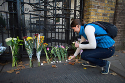 © Licensed to London News Pictures. 01/11/2015. London, UK. A young russian woman lights a candle next to flowers left at the gates to the Russian embassy in London following yesterdays plane crash in which a Russian passenger plane  flying from Sharm el Sheikh to St Petersburg crashed killing all the passengers and crew.  Photo credit: Ben Cawthra/LNP