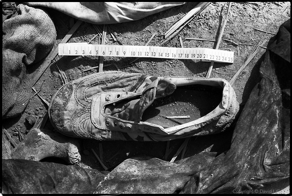 A child's shoe at a mass grave near Hillah, Iraq, where one can see the remains of men, women and children. Some remains from the site were recovered by local people and left in piles.