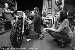 Last Chance! Scott Jones does some final prep on his bike as his mother watches (laughing) in the background and his wife Summer Jones at his side at Noise Cycles the night before Born Free 6. Santa Ana, CA. USA. June 26, 2014.  Photography ©2014 Michael Lichter.