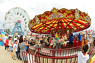 Brooklyn, New York, USA. 10th August 2013. Children ride on the Carousel horses at Luna Park, with The Wonder Wheel in the background, during the 3rd Annual Coney Island History Day celebration. Taken with 180 degree fisheye lens.