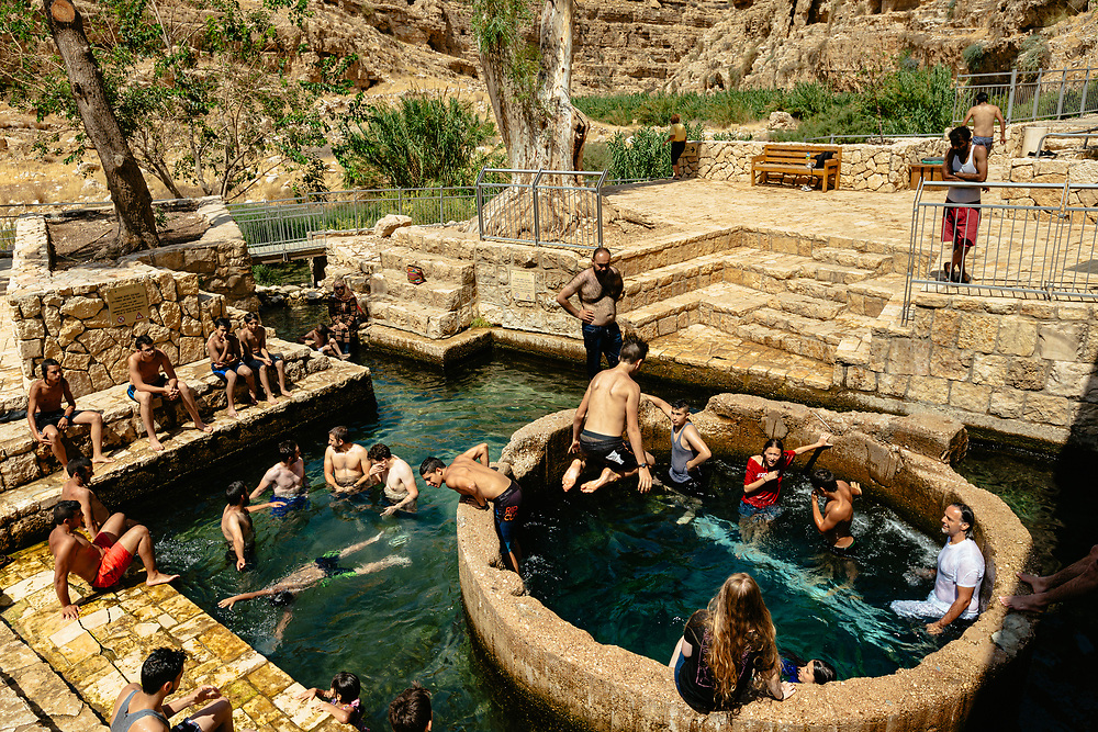 People swim at Ein Maboa (Hebrew) spring, also known as Ein Fawar in Arabic, an intermittent spring, with water levels rising and falling at various intervals, at Nahal Prat Nature Reserve in the Dead Sea region, Israel