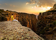 A lone hiker sits at the edge of a cliff at Black Conyon of the Gunnison National Park in southern Colorado.