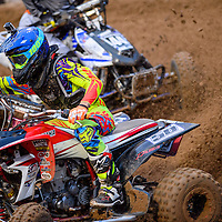 071815       Cable Hoover<br /> <br /> Quad pro racers kick up dirt as the lean into a turn during the Red Rock Arenacross Saturday at Red Rock Park.