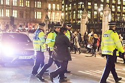 Westminster, London, December 2nd 2015.  As Parliament prepares to vote on air strikes on Islamic State terrorists in Syria, Stop The War and other groups opposed to British military involvement protest outside Parliament. PICTURED: Peace protester Maria Gallastegui is led away by police after having gone under a 16 tonne truck. ///FOR LICENCING CONTACT: paul@pauldaveycreative.co.uk TEL:+44 (0) 7966 016 296 or +44 (0) 20 8969 6875. ©2015 Paul R Davey. All rights reserved.