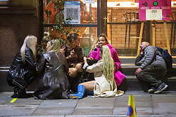 © Licensed to London News Pictures. 10/10/2020. Manchester, UK. People sit on the pavement outside a bar on Peter Street after closing time . People out in pubs, bars and restaurants in Manchester City Centre ahead of the currently imposed daily 10pm curfew . Millions of people across the north of England are waiting to learn if the British Government will impose a regional lockdown on Monday (12th October 2020), as Coronovirus infection rates continue to rise rapidly . Photo credit: Joel Goodman/LNP