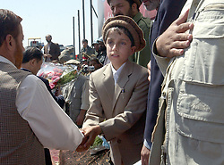 KABUL,AFGHANISTAN - SEPT. 9: Ahmad Massoud, the son of the slain leader Ahmad Shah Massoud  shakes hands of dignitaries and guests during a ceremony in Kabul Sports Stadium September 9, 2002  to commemorate  the one-year anniversary of the death of his father.   (Photo by Ami Vitale/Getty Images)