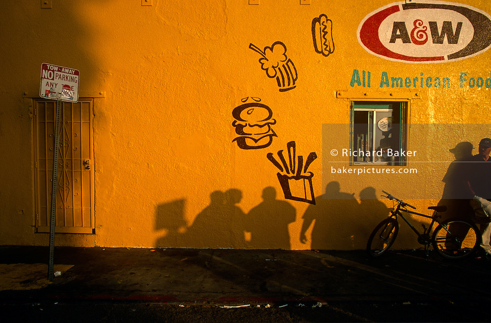 Shadows from crowds play across the bright yellow-painted wall near Venice Beach in Santa Monica.