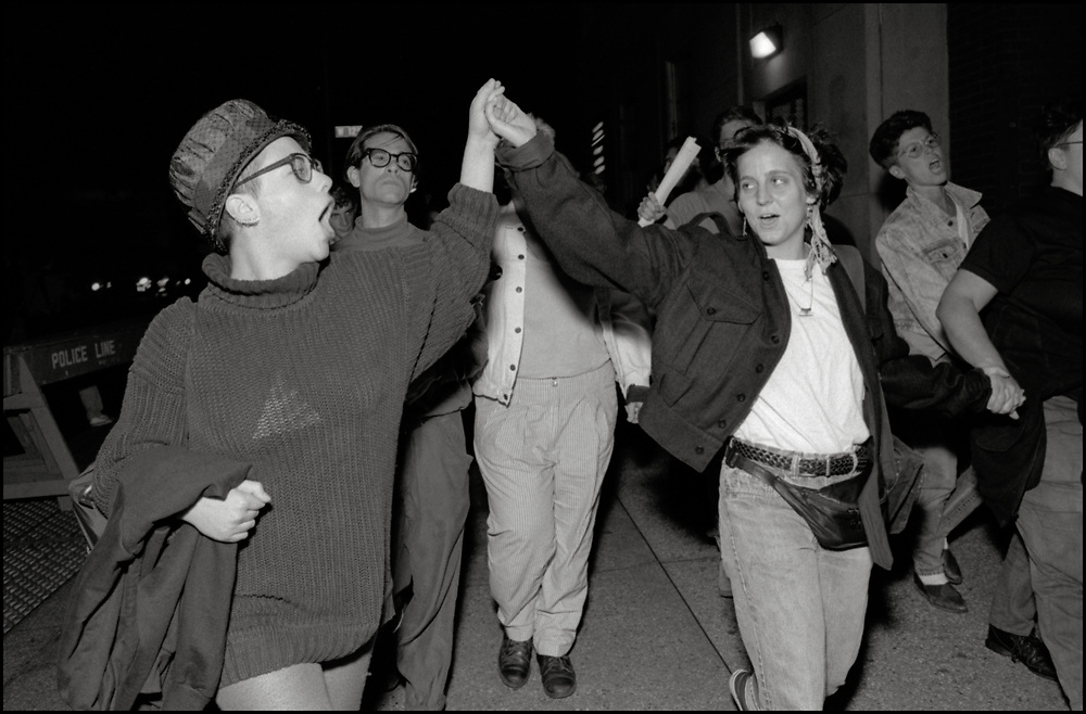 At a Monday night ACT UP meeting in September 1989, it was brought to the floor that a gay man had been kicked out of the ER at St. Vincents Hospital by a security guard because he had dared to kiss his lover. A heated conversation ensued and eventually the whole room got up, walked around the corner to the hospital and took over the waiting room in the ER. As a result, the hospital agreed to meet with representatives of ACT UP. <br /> <br /> Several ACT UP members met with the president of the hospital and the executive board, which resulted in sensitivity training for all of their employees.<br /> <br /> Neil Broome, Garance Franke-Ruta and others on their way from The Center to St. Vincents Hospital.