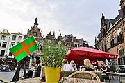 Nederland, Nijmegen, 18-7-2020 Voor het eerst sinds de oorlog wordt er geen 4 daagse gehouden dit jaar . Alleen in 2006 werd deze na een dag afgelast vanwege de hitte . Nu is de afgelasting het gevolg van de coronadreiging . De stichting vierdaagsefeesten brengt toch een feestelijk tintje in de stad aan door boven de winkelstraten vierdaagsevlaggetjes te hangen. Ook de terrassen krijgen deze linten zodat ze hun terrasje kunnen opvrolijken. Sommige horecazaken hebben dat al gedaan . De grote vierdaagsevlag hangt ook uit bij diegene die deze hebben . De kastanjeboom voor het gemeentehuis is volgens traditie volgehangen met gladiolen . Veel ondernemers, winkels en horeca, in het stadscentrum lijden grote verliezen door het wegvallen van de feesten . De vierdaagsefeesten zijn het grootste meerdaagse festival van het land . Foto: ANP/ Hollandse Hoogte/ Flip Franssen