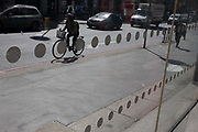 Cyclists pedal past an office foyer entrance featuring dots and circles on exterior windows in the City of London. As the rider passes-by, the spots on the window repeat on the wheels of the bike on a bright day, where contrast is high and shadows deep. Traffic has made its way northwards across London Bridge from the southern bank to the city itself on the north. There is little colour, a scene of monochrome - of greys and blacks.