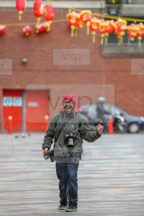 A photographer is seen wondering around deserted China Town in London, Britain, on Sunday, May 3, 2020. (Photo/ Vudi Xhymshiti)