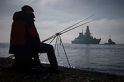© Licensed to London News Pictures. 02/11/2017. Portsmouth, UK.  A man fishing as HMS Dragon sails into her home port of Portsmouth for the first time in two months.  The Type 45 destroyer has been on a deployment involving exercises with the U.S. Navy and also a visit to the British Overseas Territory of Gibraltar.  Photo credit: Rob Arnold/LNP