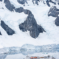 The National Geographic Explorer is dwarfed by the grandiose mountain landscape while anchored in Port Charcot at Booth Island, Antarctica.