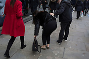 A lady who has momentarily dropped her bag is helpd to recover herself by a man in the street, on 19th December 2018, in London, England.