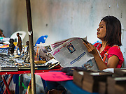 27 NOVEMBER 2015 - BANGKOK, THAILAND: An amulet vendor reads a Thai newspaper while she waits for customers at her amulet stand on Maharat Road in Bangkok. Hundreds of vendors sell amulet and Buddhist religious paraphernalia to people in the Amulet Market, a popular tourist attraction along Maharat Road north of the Grand Palace near Wat Maharat in Bangkok. Bangkok municipal officials announced that they are closing the market and forcing vendors to relocate to an area about one hour outside of Bangkok. The closing of the amulet market is the latest in a series of municipal efforts to close and evict street vendors and markets from areas that have potential for redevelopment. The street vendors will be evicted from the area by Sunday, Nov. 29.    PHOTO BY JACK KURTZ