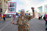 Sylvia Collins holds a sign and a raised fist in solidarity witht the students who organized the March for Our Lives march in front of Dallas City Hall in downtown Dallas.