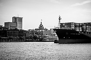 Savannah, Georgia, USA - July 29, 2021: The container ship Northern Precision sails past River Street and the historic heart of the city as it departs the Port of Savannah.