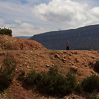 Africa, Morocco, Tansghart. Woman on road of Tansghart in the Atlas Mountains.