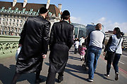 Hassidic Jewish men walking over Westminster Bridge on a day out, London, UK.