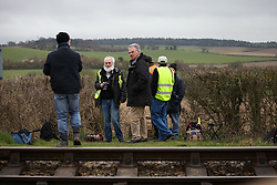 © Licensed to London News Pictures. 07/03/2014. Hampshire, UK. Train spotters waiting at a footpath crossing along the Watercress Line today, 7th March 2014, which is the first day of the 'spring steam gala' on the Watercress Line. The railway line, operated by Mid Hants Railway Ltd, passes between Alresford and Alton in Hampshire. The line is named after its use in the past for transporting freshly cut watercress from the beds surrounding Alresford to London. Photo credit : Rob Arnold/LNP