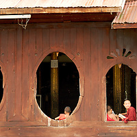 Novice monks at the window of monastery at Nyaungshwe