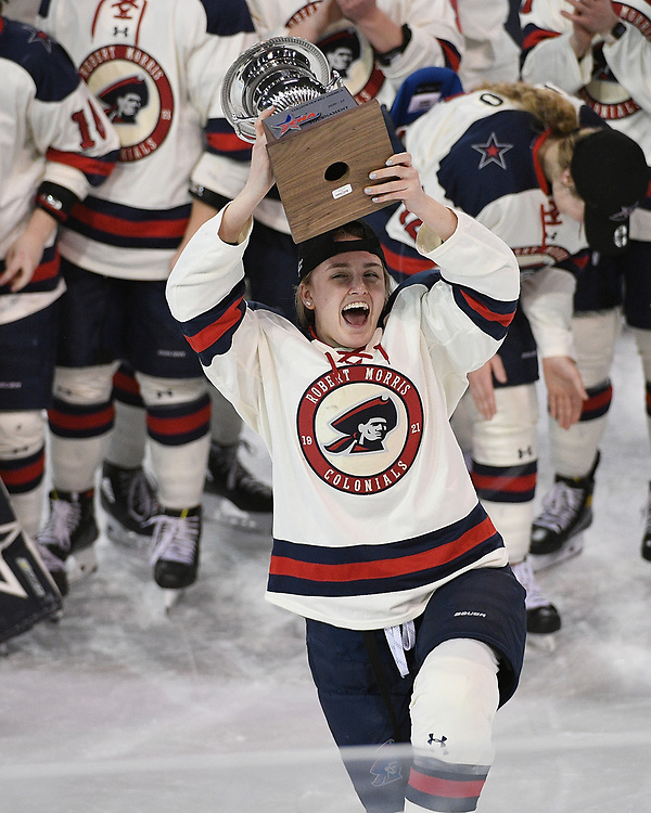 ERIE, PA - MARCH 06: Allyson Hebert #4 of the Robert Morris Colonials hoists the CHA Championship Trophy after the Colonials defeated the Syracuse Orange 1-0 in the championship game at the Erie Insurance Arena on March 6, 2021 in Erie, Pennsylvania. (Photo by Justin Berl/Robert Morris Athletics)
