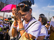 06 JANUARY 2013 - BANGKOK, THAILAND:  A woman prays with a Buddhist prayer bell at a shrine in Bangkok during a service for a relic of the Buddha's hair. The relic has been on display in Bangkok for about 10 years. There was a ceremony in Sanam Luang in Bangkok Sunday to honor the relic. People prayed for it and received blessings from Buddhist monks and Brahmin priests who presided over the service. The hair is being moved to Ayutthaya, where it will be displayed in a Buddhist temple. The piece of hair has been on loan to Thai Buddhists from a Buddhist temple in Sri Lanka.   PHOTO BY JACK KURTZ