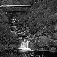 This New Hampshire B&W landscape photography image of New England fall foliage peak colors at the Liberty Gorge at the Franconia Notch State Park near Lincoln, New Hampshire features the Sentinel Pine Bridge spanning across this beautiful New England gorge and a series of small waterfalls and cascades rushing into The Pool. The pool is a deep basin in the Pemigewasset River and was formed at the end of the ice age. <br />