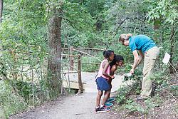 Educator teaching children about tree identification, Dogwood Canyon Audubon Center, Cedar Hill, Texas, USA.