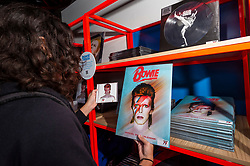 © Licensed to London News Pictures. 25/10/2021. LONDON, UK. A Bowie fan browses merchandise at the opening of a David Bowie pop-up shop in Heddon Street in the West End.  Open 75 days before the late singer's 75th birthday, the pop-up is located close to where Bowie posed as Ziggy Stardust on the cover of his 1972 album The Rise and Fall of Ziggy Stardust and the Spider from Mars.  The store sells limited edition records and memorabilia curated by his estate and will be open until January 2022. A sister shop will open in New York and both form part of a year long celebration of David Bowie's 75th birthday.  Photo credit: Stephen Chung/LNP