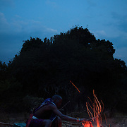 The Stars Foundation visiting S.A.F.E in the Loita Hills near the Tanzanian border in Kenya...It is mainly Maasais who live in the Loita Hills up above the Serengeti plains. They live in small villages and communities called bomas and live mainly of raising and selling live stock such as cattle and goats. Its a very remote region in Kenya, hard to get to without a four wheel drive with very little infrastructure and up till 2010 no mobile phone network. The Maasais are well known though out Kenya and the world for their colorful clothing and their way of keeping their old traditions alive...Dixon is cooking his dinner, cows spare ribs. Meat is an important part of the Maasai's diet, as well as maze and milk. Dixon is a member of the S.A.F.E theatre group. S.A.F.E is a charity which educates children and young people about life skills and how to protect themselves from HIV and other STIs through performance. They also do performances about Female Genital Mutilation, an old tradition amongst the Maasais in Loita and a very brutal and controversial custom which S.A.F.E is trying to eradicate.