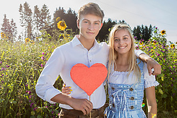 Teenage couple with heart shape in front of sunflower field, Bavaria, Germany