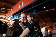 Anastasia Dobromyslova and fellow Russian-born friend Irena Armstrong check text messages during the ladies darts tournament.